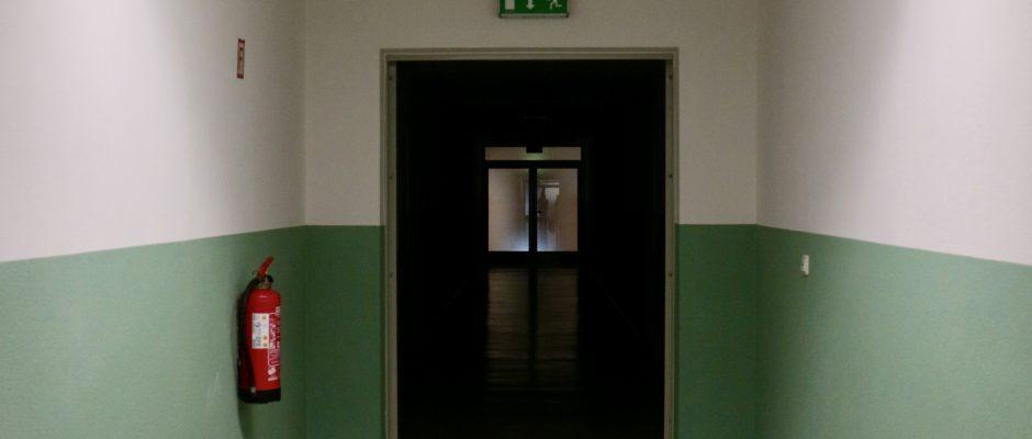 leerer Raum, vermutlich Flur mit Feuerlöscher und einem Notausgangsschild über einer Tür im Zentrum. Eine Neonröhre befindet sich an der Decke. Die hälfte des Raums und der Dekce ist weiß, die untere Hälfte minzgrün.