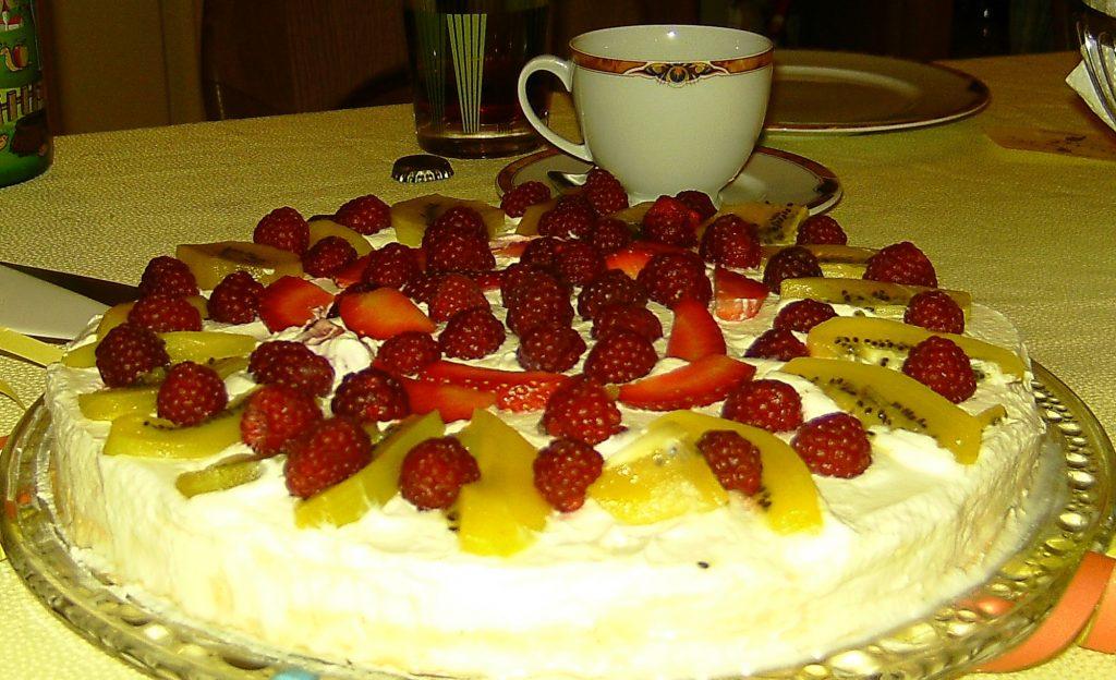 Neuseeländische Pavolva (ähnlich Baiser-Torte) mit Kiwis, Himbeeren und Erdbeeren