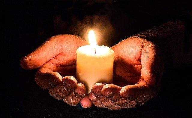Offene Hände halten eine brennente Kerze