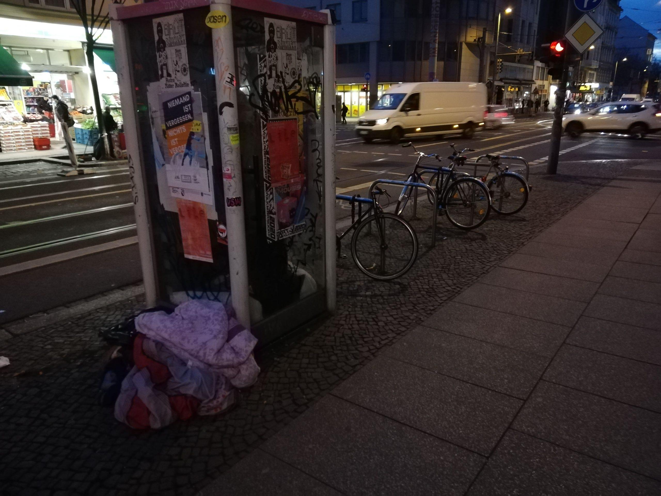 Man Sieht die TelefonZelle auf der Eisenbahnstraße in der eine unkenntliche Gestalt steht. An und in der Telefonzelle sind verschiedene Decken und Plasiktüten angelehnt. Es ist Nacht. Im Hintergrund erkennt man einige Geschäfte und verschwommen auch Passanten.