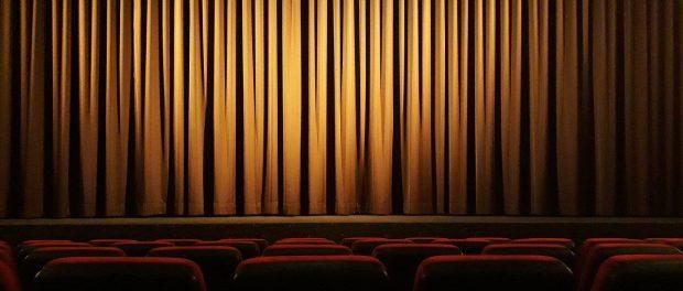 leerer Theatersaal mit zugezogenem gelblichen Vorhang